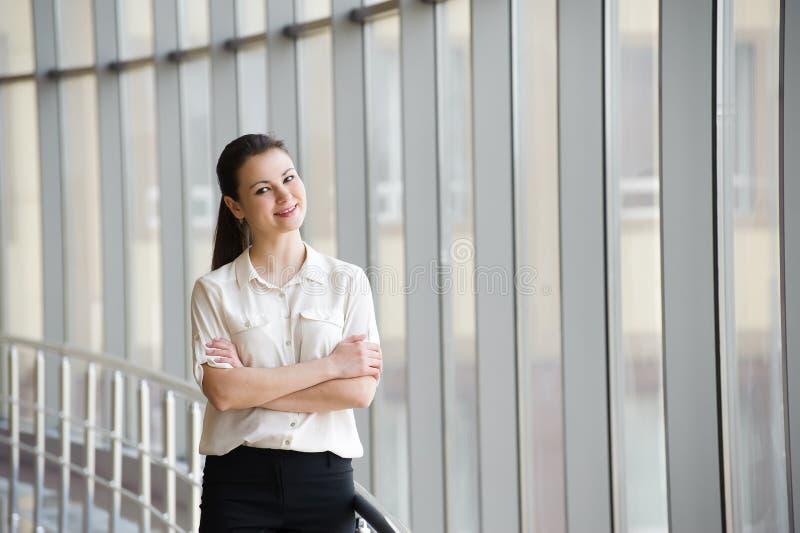 Junge Geschäftsfrau, die am Handy beim Bereitstehen des Fensters im Büro spricht Schönes junges weibliches Modell im Büro lizenzfreie stockfotos