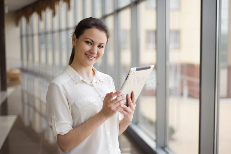 Junge Geschäftsfrau, die am Handy beim Bereitstehen des Fensters im Büro spricht Schönes junges weibliches Modell im Büro stockfotografie