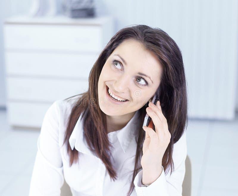 Junge Geschäftsfrau, die am Handy im Büro spricht stockfoto