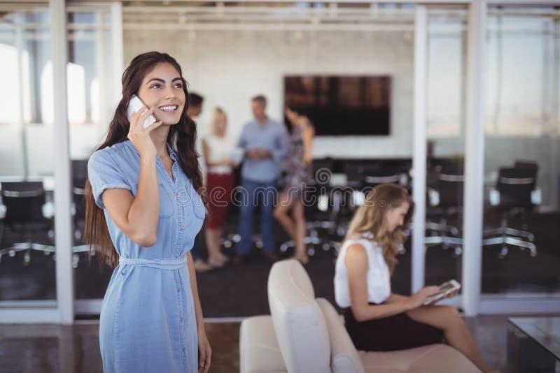 Junge Geschäftsfrau, die am Handy im kreativen Büro spricht stockfoto