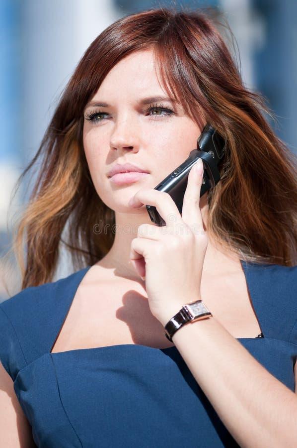 Junge Geschäftsfrau, die Handy verwendet stockfoto