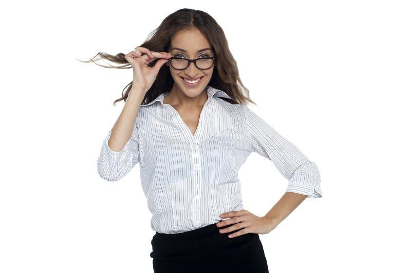 Junge Geschäftsfrau, die ihre Schauspiele justiert lizenzfreie stockfotos