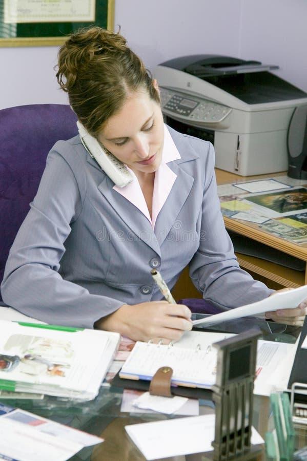 Junge Geschäftsfrau, die in ihrem Büro arbeitet lizenzfreies stockfoto