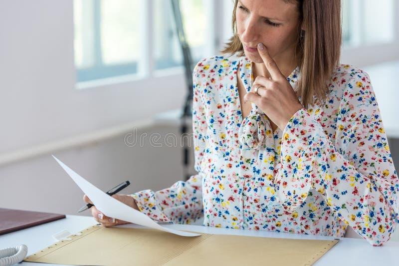 Junge Geschäftsfrau, die an ihrem Schreibtisch arbeitet lizenzfreie stockfotografie
