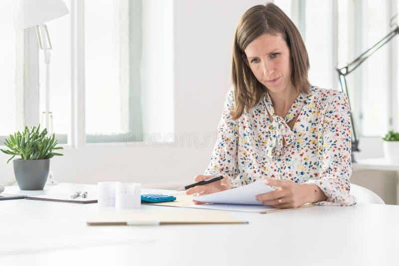Junge Geschäftsfrau, die an ihrem Schreibtisch mit Dokumenten arbeitet stockfotografie