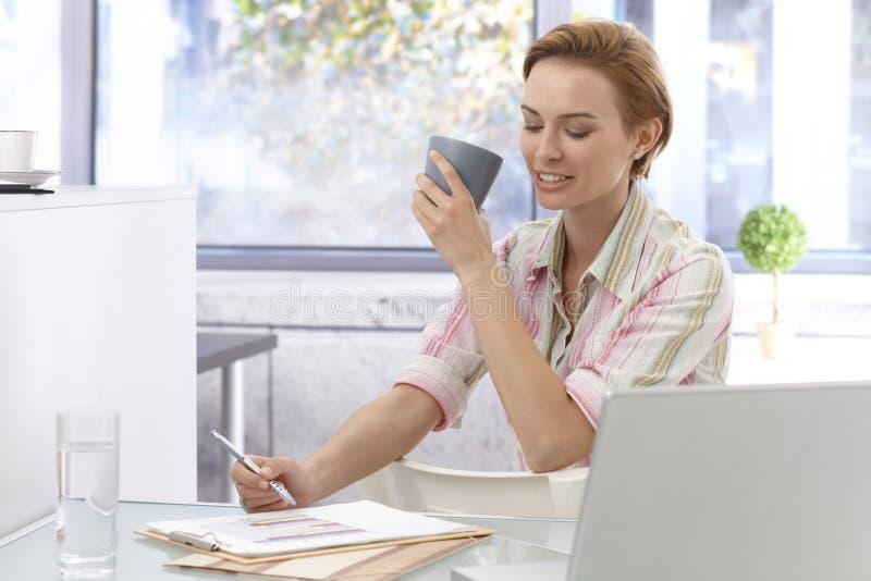 Junge Geschäftsfrau, die im Büro arbeitet stockfotografie