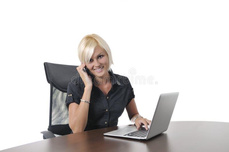 Junge Geschäftsfrau, die im Büro auf Laptop arbeitet lizenzfreie stockbilder