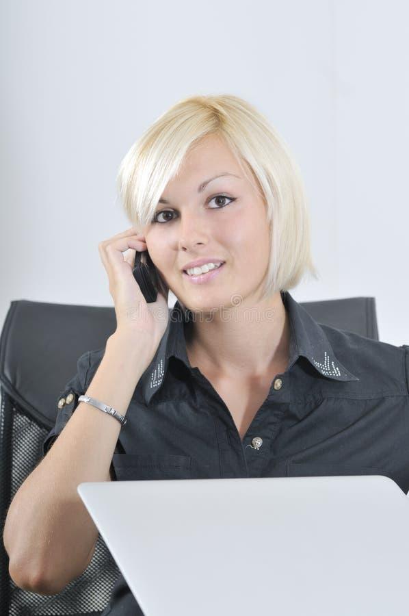 Junge Geschäftsfrau, die im Büro auf Laptop arbeitet stockfoto