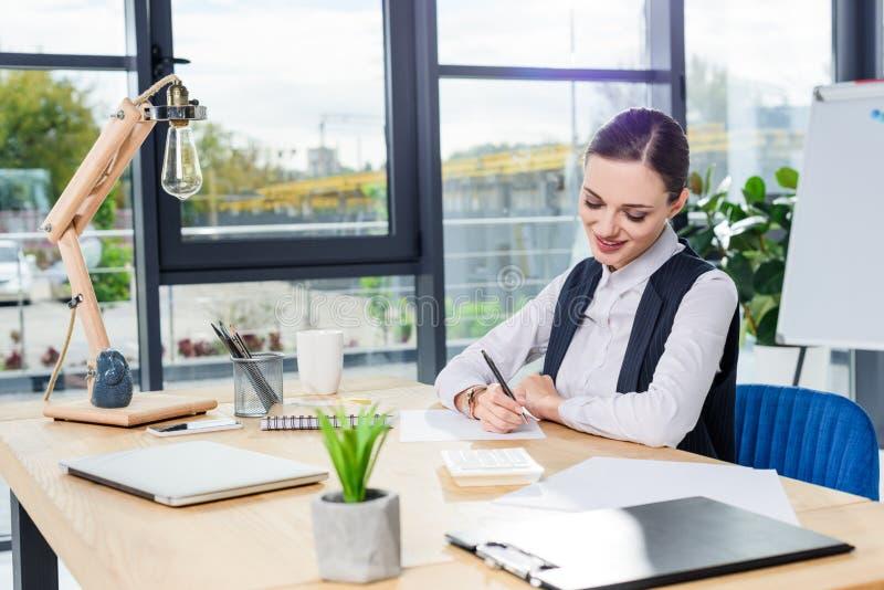 Junge Geschäftsfrau, die im Büro an ihrem Schreibtisch sitzt und Anmerkungen auf Stück schreibt lizenzfreie stockfotografie