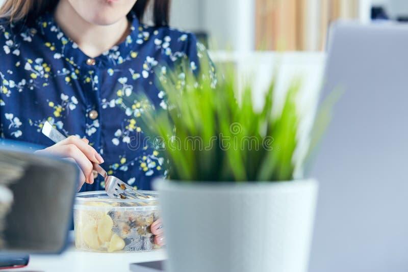 Junge Geschäftsfrau, die im Büro mit einem Laptop unter Verwendung des drahtlosen Internets, zu Mittag essend sitzt lizenzfreies stockfoto