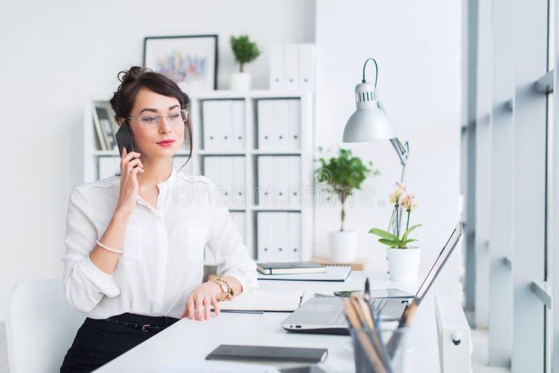 Junge Geschäftsfrau, die im Büro, schreibend, unter Verwendung des Computers arbeitet Starke Frau, die online Informationen sucht stockfotografie