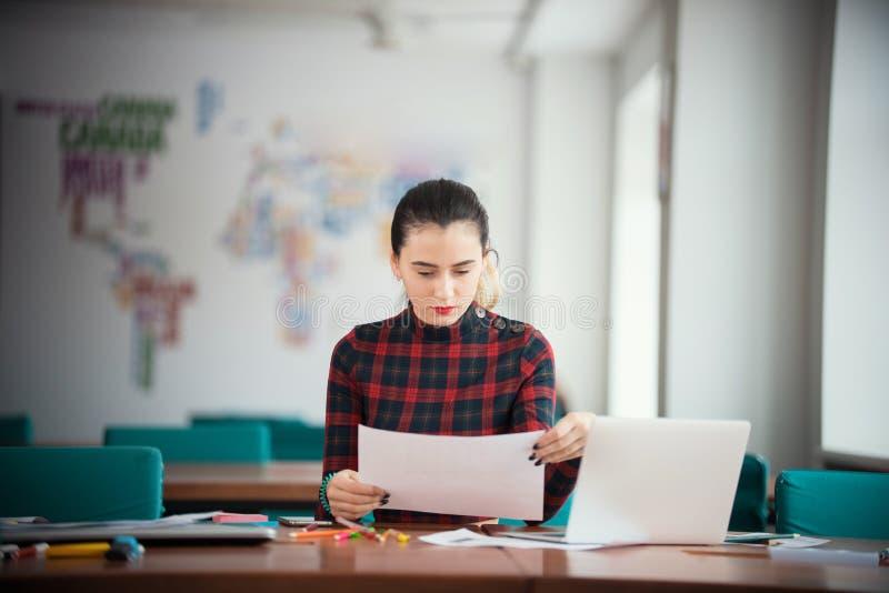 Junge Geschäftsfrau, die im Büro sitzt durch die Tabelle arbeitet Betrachten von Papieren lizenzfreies stockfoto