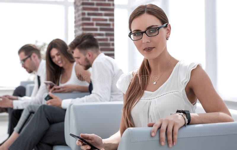 Junge Geschäftsfrau, die im Bürowarteraum sitzt lizenzfreie stockfotografie