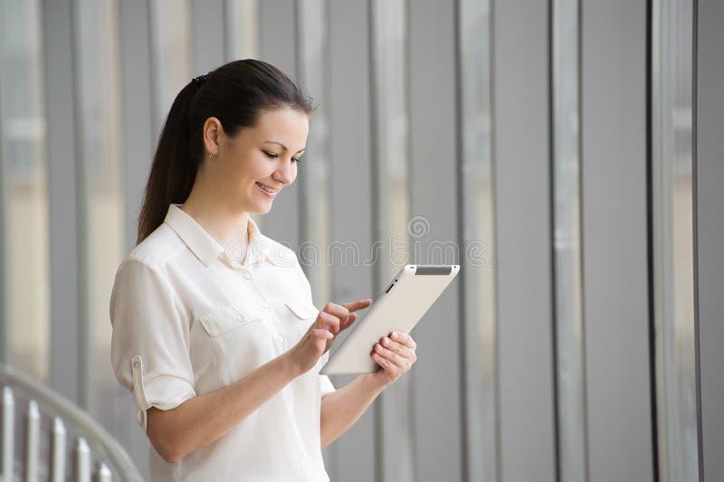 Junge Geschäftsfrau, die an ipad beim Bereitstehen des Fensters im Büro arbeitet Schönes junges weibliches Modell im Büro lizenzfreie stockfotos