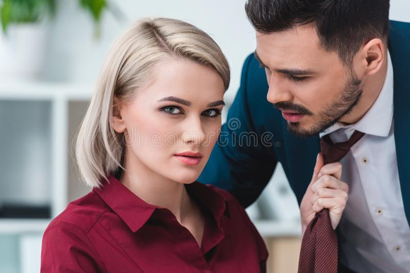 junge Geschäftsfrau, die Kamera beim Halten der Krawatte von betrachtet stockbilder