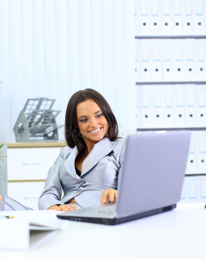 Junge Geschäftsfrau, die an Laptop arbeitet stockfoto