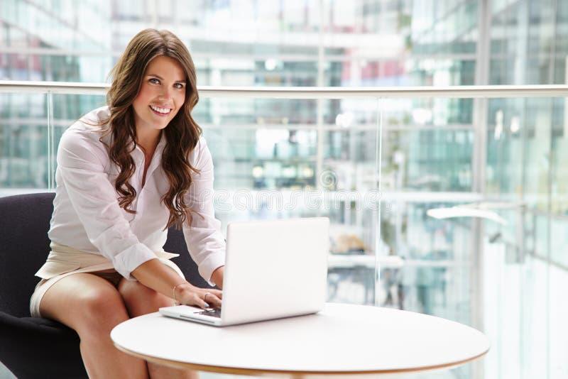 Junge Geschäftsfrau, die Laptop-Computer im modernen Innenraum verwendet stockfotografie