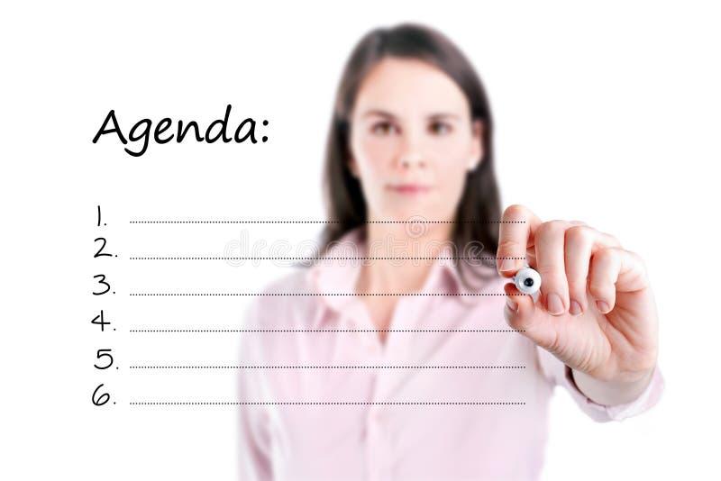 Junge Geschäftsfrau, die leere Tagesordnungsliste schreibt. stockbilder