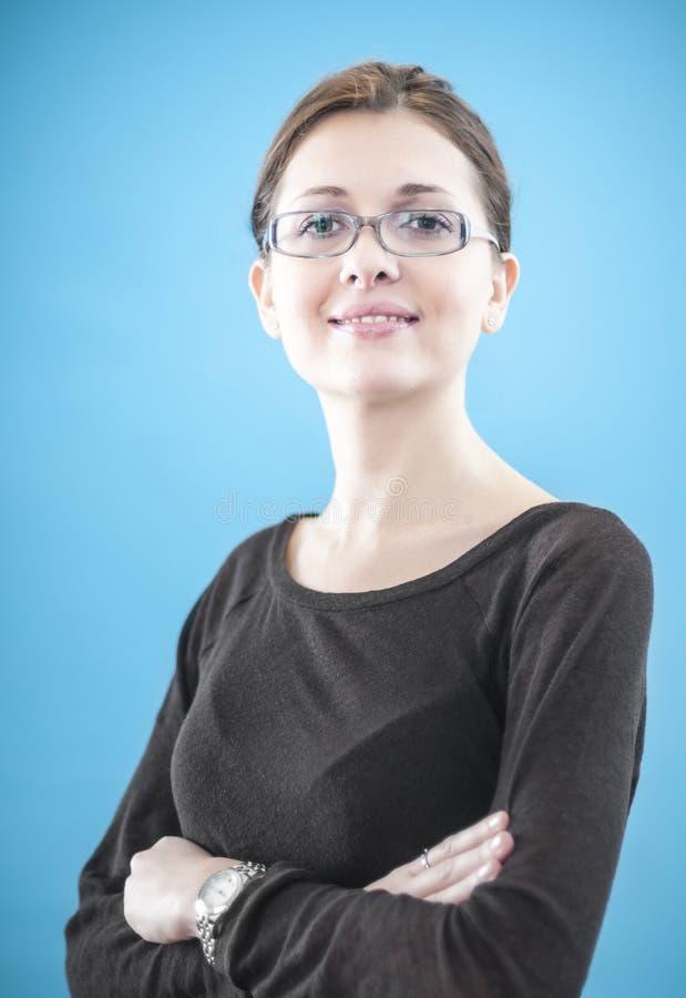 Junge Geschäftsfrau, die mit den gefalteten Händen steht stockfotografie