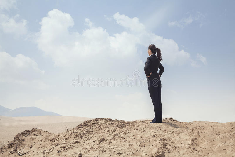 Junge Geschäftsfrau, die mit den Händen auf den Hüften heraus schauen über der Wüste steht stockfoto