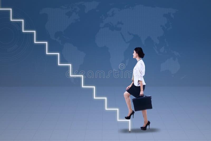 Junge Geschäftsfrau, die oben auf Treppe geht lizenzfreies stockbild