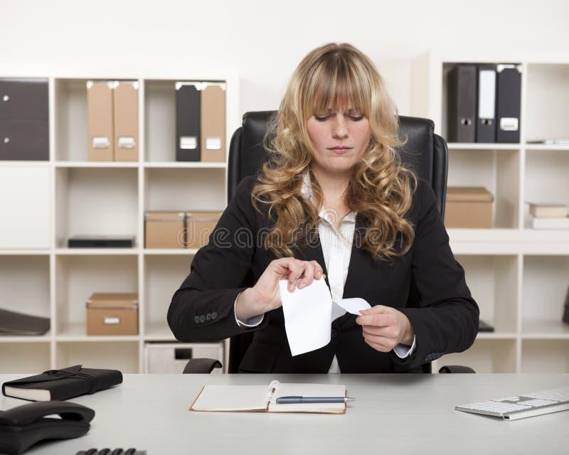 Junge Geschäftsfrau, die oben ein Dokument zerreißt lizenzfreies stockfoto