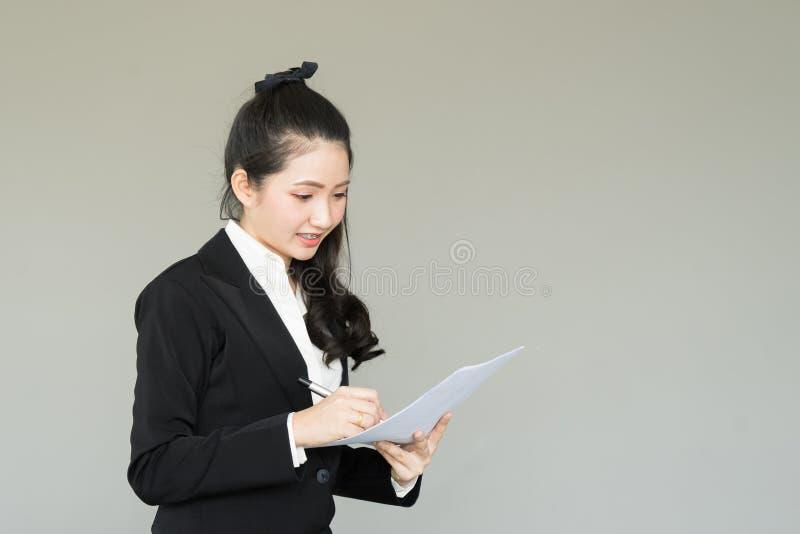 Junge Geschäftsfrau, die Papier, Schreibensanmerkung hält lizenzfreies stockfoto