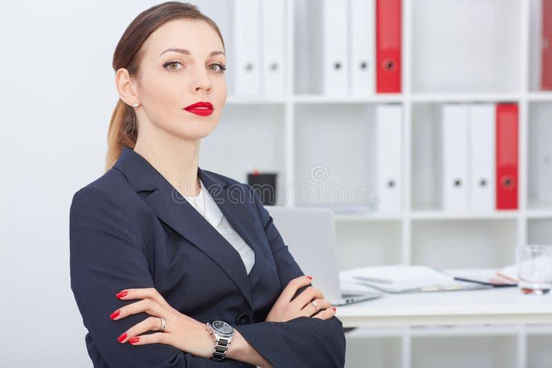 Junge Geschäftsfrau, die sicher der Kamera vor dem hintergrund der Büroräume betrachtet stockfotografie