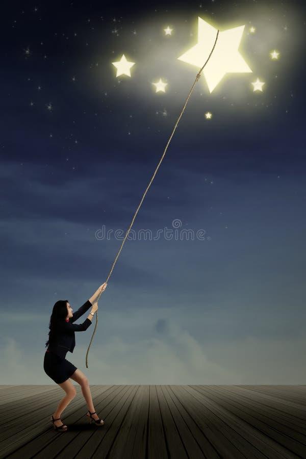 Junge Geschäftsfrau, die Sterne nimmt lizenzfreie abbildung