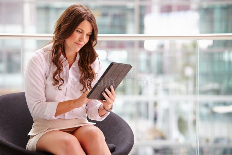 Junge Geschäftsfrau, die Tablet-Computer im modernen Innenraum verwendet lizenzfreie stockbilder