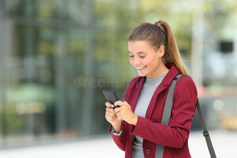 Junge Geschäftsfrau, die Telefon auf der Straße verwendet stockfotografie