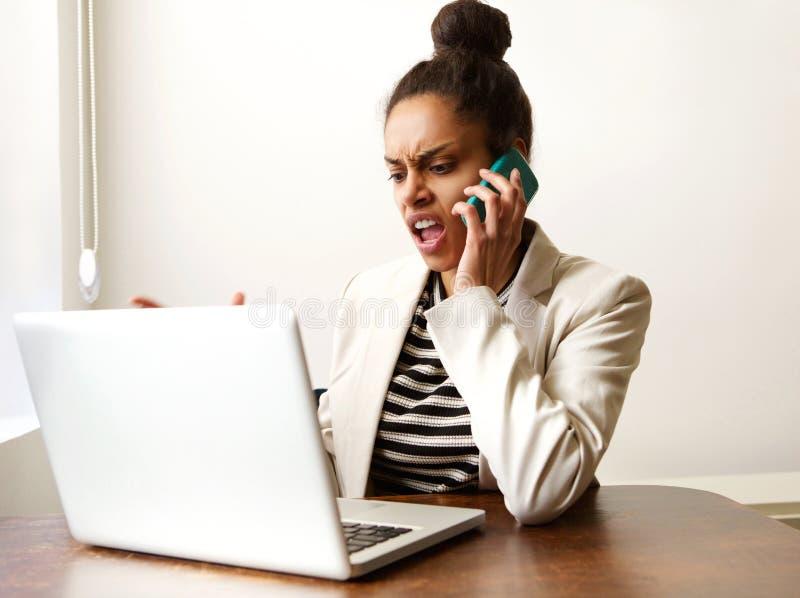 Junge Geschäftsfrau, die am Telefon schreit lizenzfreies stockfoto
