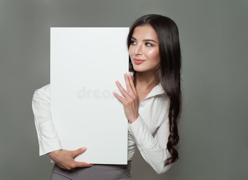 Junge Geschäftsfrau, die weiße Fahne des leeren Papiers hält stockfotografie