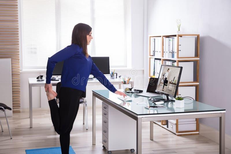 Junge Geschäftsfrau, die Yoga tut stockfoto
