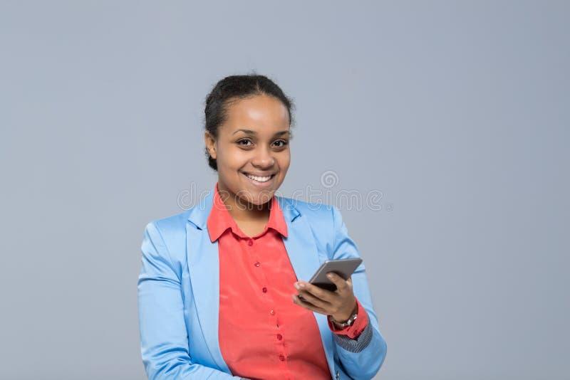 Junge Geschäftsfrau, die Zellintelligentes Telefon-Afroamerikaner-Mädchen-glückliche Lächeln-Geschäftsfrau verwendet stockbild