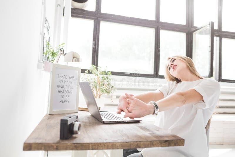 Junge Geschäftsfrau, die zu Hause hinter einem Laptop arbeitet und ihre Hände ausdehnt Kreativer skandinavischer Artarbeitsplatz lizenzfreies stockbild