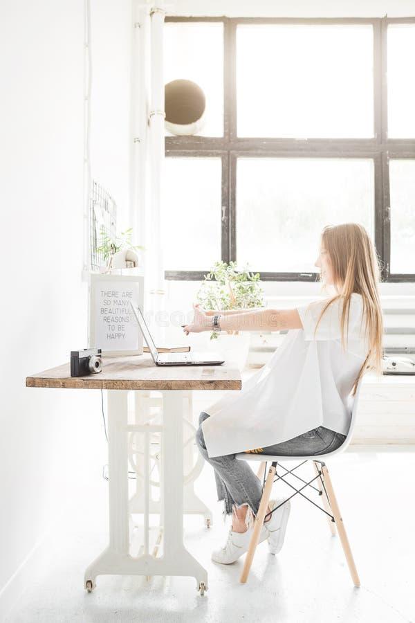 Junge Geschäftsfrau, die zu Hause hinter einem Laptop arbeitet und ihre Hände ausdehnt Kreativer skandinavischer Artarbeitsplatz lizenzfreie stockbilder