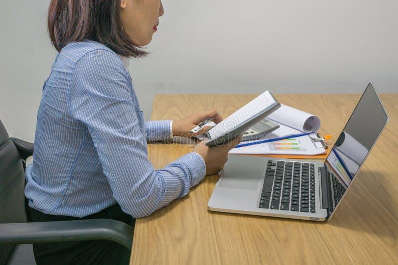 Junge Geschäftsfrau Finanzdokument im Büro berechnen lizenzfreie stockbilder