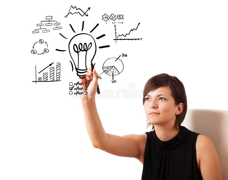 Junge Geschäftsfrau, Glühlampe mit den verschiedenen Diagrammen zeichnend lizenzfreies stockbild