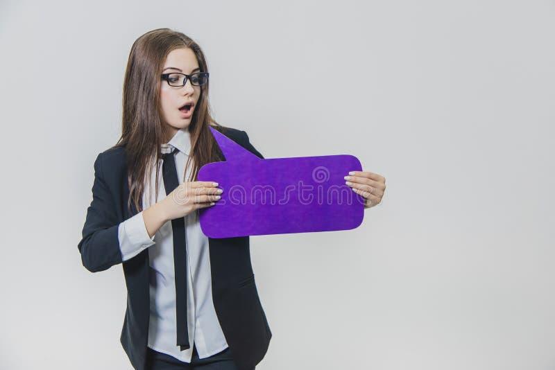 Junge Geschäftsfrau hält ein violettes Spracheblase closse zu, das rechteckig ist, auf lizenzfreies stockfoto