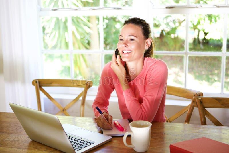 Junge Geschäftsfrau an ihrem Schreibtisch und Unterhaltung am Handy lizenzfreie stockbilder