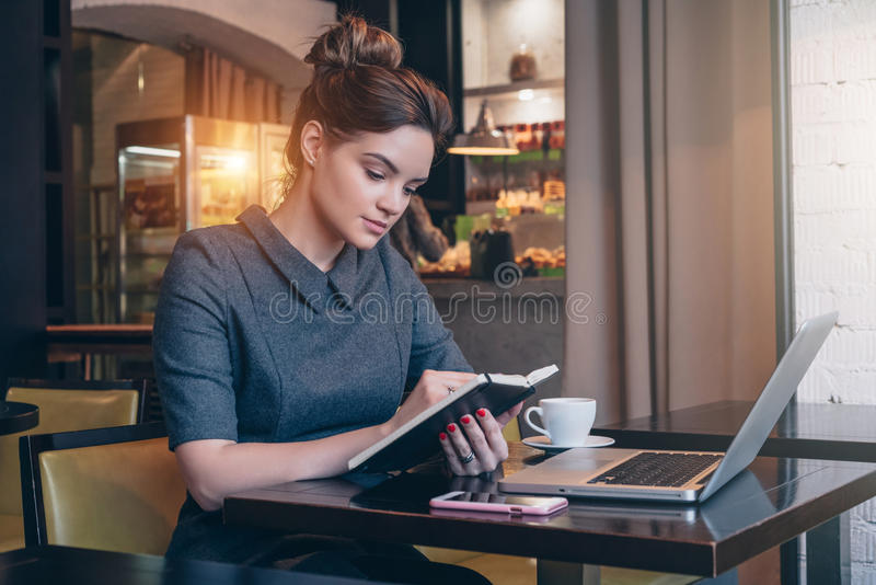 Junge Geschäftsfrau im grauen Kleid, das bei Tisch im Kaffeestube- und Lesebuch sitzt stockfoto