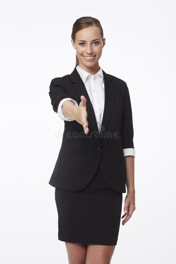 Junge Geschäftsfrau im Studio, Hände rüttelnd stockbild