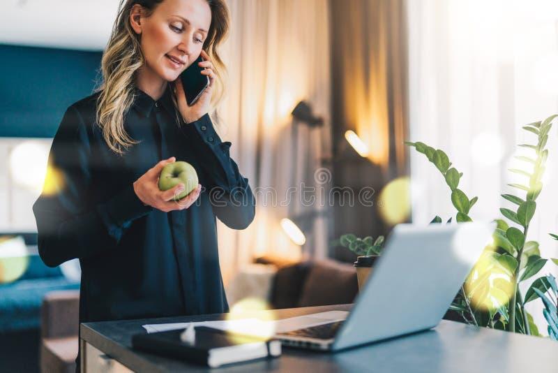 Junge Geschäftsfrau ist stehende nahe Innentabelle vor Computer, bei der Unterhaltung am Handy und dem Halten des Apfels stockfotos