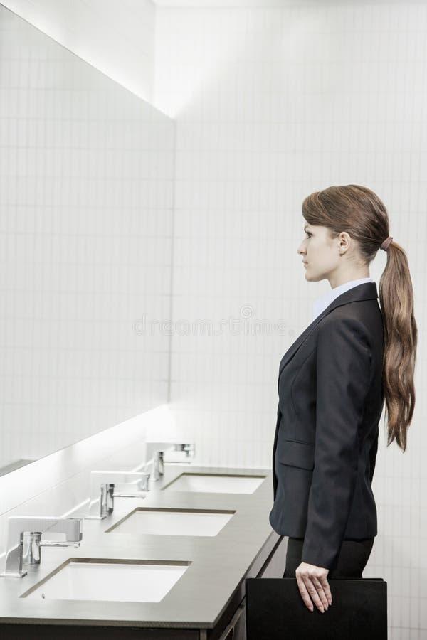 Junge Geschäftsfrau mit dem langen Haar, das den Spiegel untersucht und im Badezimmer sich vorbereitet stockbilder