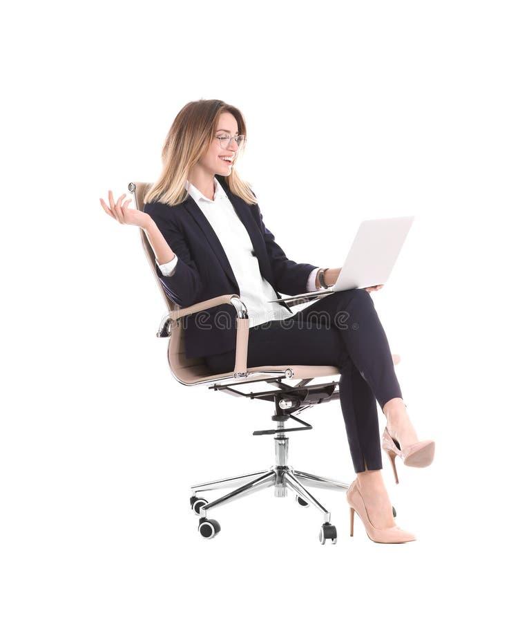 Junge Geschäftsfrau mit dem Laptop, der im Bürostuhl sitzt stockfoto