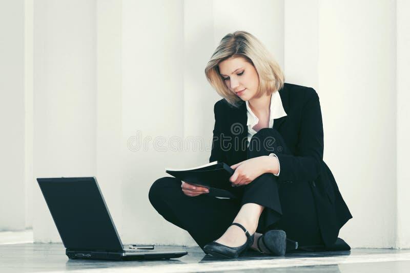Junge Geschäftsfrau mit dem Laptop, der an der Wand sitzt stockbilder
