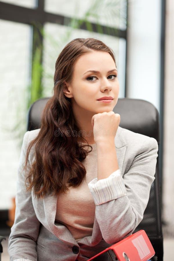 Junge Geschäftsfrau mit den Faltblättern, die im Stuhl sitzen stockfoto