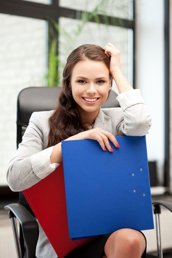 Junge Geschäftsfrau mit den Faltblättern, die im Stuhl sitzen lizenzfreie stockfotos