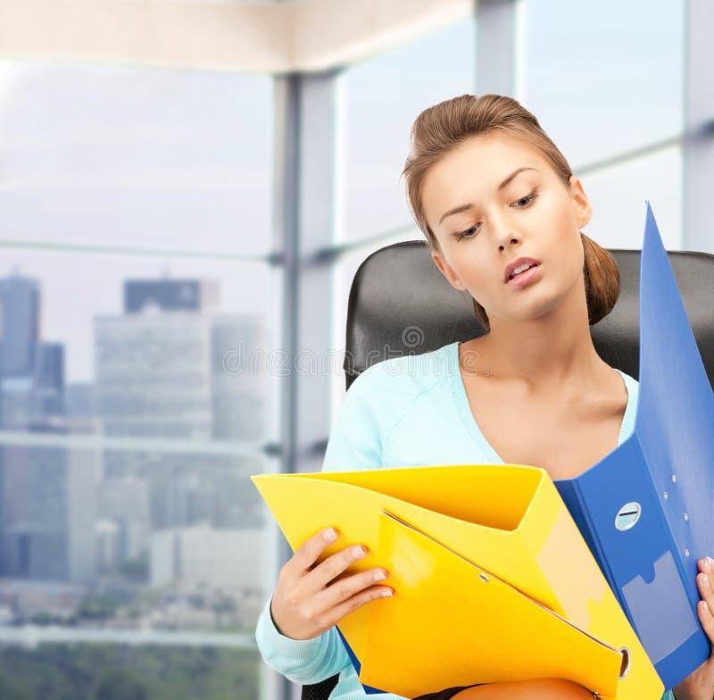 Junge Geschäftsfrau mit den Faltblättern, die im Stuhl sitzen stockbilder